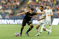 FOXBOROUGH, MA - AUGUST 4: Eduard Atuesta #20 of Los Angeles FC dribbles as Edgar Castillo #8 of New England Revolution defends during a game between Los Angeles FC and New England Revolution at Gillette Stadium on August 3, 2019 in Foxborough, Massachusetts.