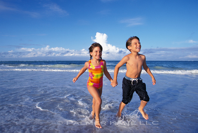 Brother and Sister Frolic in the Surf along the Beach on Sunshine Key, Sarasota, FL, USA