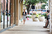 Attractive blonde woman looking in the window of the store at an Austin outdoor shopping mall.