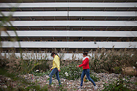 Two young women walk past a Yue Yuen Industrial Holdings Limited factory dormitory building in Dongguan, Guangdong Province, China, 03 March 2015.
