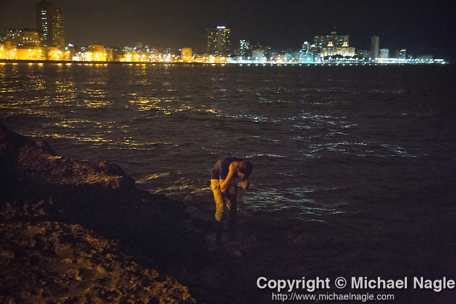 HAVANA, CUBA -- MARCH 24, 2015:   A man bathes along the Malecon in Havana, Cuba on March 24, 2015. Photograph by Michael Nagle