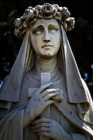 A statue of Saint Rose stands in a landscaped setting facing St. Rose Hospital in Hayward, California.