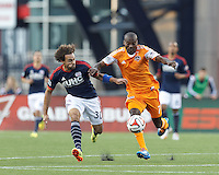 Houston Dynamo substitute forward Omar Cummings (7) works to clear ball as New England Revolution defender Kevin Alston (30) defends. In a Major League Soccer (MLS) match, the New England Revolution (blue/white) defeated Houston Dynamo (orange), 2-0, at Gillette Stadium on April 12, 2014.