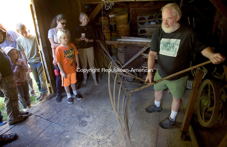 MIDDLEBURY CT. 28 September 2013-092813SV06-At right, Rob Fenn of Middlebury shows off an old farming tool during the Fenn's Farm open house and annual tour in Middlebury Saturday.<br /> Steven Valenti Republican-American