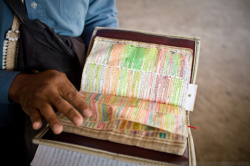 An evangelist shows his Bible. He drove over his 1 year old child when drunk 4 years ago..Nauruans are extremely fervent believers of the Christian faith...Nauru, officially the Republic of Nauru is an island nation in Micronesia in the South Pacific.  Nauru was declared independent in 1968 and it is the world's smallest independent republic, covering just 21 square kilometers..Nauru is a phosphate rock island and its economy depends almost entirely on the phosphate deposits that originate from the droppings of sea birds. Following its exploitation it briefly boasted the highest per-capita income enjoyed by any sovereign state in the world during the late 1960s and early 1970s..In the 1990s, when the phosphate reserves were partly exhausted the government resorted to unusual measures. Nauru briefly became a tax haven and illegal money laundering centre. From 2001 to 2008, it accepted aid from the Australian government in exchange for housing a Nauru detention centre, with refugees from various countries including Afghanistan and Iraq..Most necessities are imported on the island..Nauru has parliamentary system of government. It had 17 changes of administration between 1989 and 2003. In December 2007, former weight lifting medallist Marcus Stephen became the President.