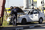 Israeli security forces inspect a car used by a Palestinian woman who, the Israeli military said, rammed it into an Israeli soldier before she was shot dead by the Israeli troops, at a main junction near the Israeli settlement bloc, Gush Etzion in the West Bank March 4, 2016. Photo by Wisam Hashlamoun