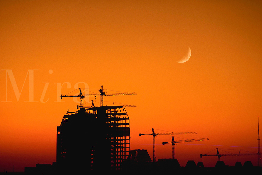 Warm sunset colors and a crescent moon add to this scene of an office building under construction.