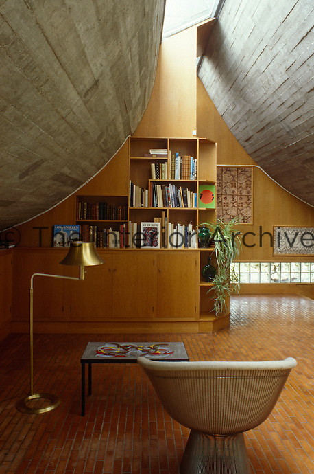 A chair by Warren Platner faces the  bookcase in the library and tv room.