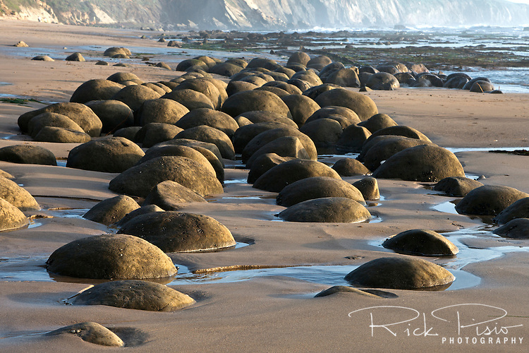 The spherical sandstone concretions on Bowling Ball Beach lie within Schooner Gulch State Beach along the Mendocino coastline in California and can only be seen at low tide.
