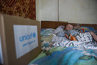 hydrocephalus child lies on the bad next to UNICEF humanitarian aid box delivered by volounteers in Yasinuvata, Eastern Ukraine, Monday, 1 June, 2015