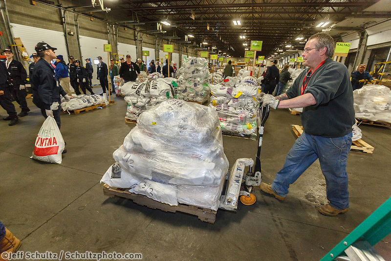 A crew of volunteers, including a group from the Alaska Military Youth Academy, move, weigh and stack thousands of musher food drop bags that are headed to the 22 checkpoints along the trail at the Airland Transport facility in Anchorage, Alaska on Wednesday, February 17, 2016 just prior to Iditarod 2016
