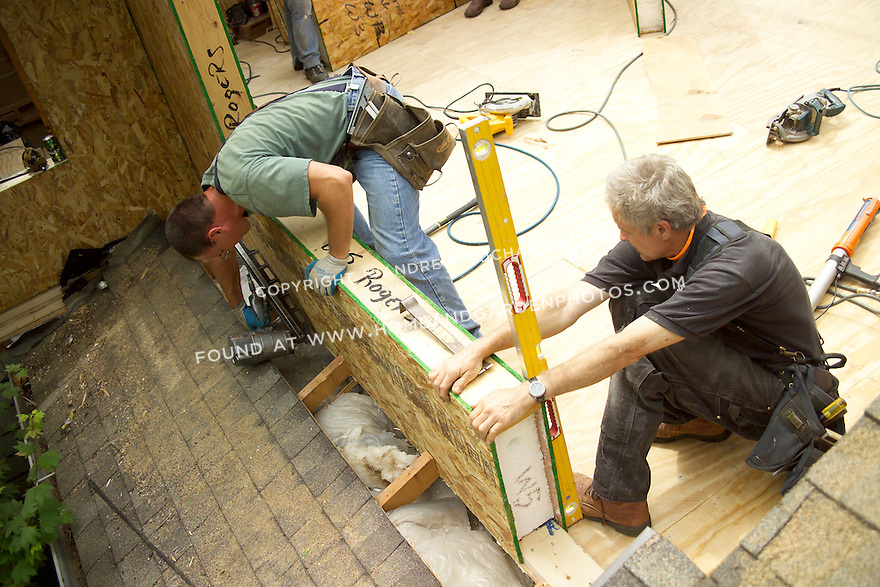 """Pulling a pre-fabricated structurally insulated panel into shape and nailing it in place on a residential remodel project outside Seattle.  SIP's laminate a 6-8"""" thick layer of strofoam between two OSB boards in pre-made shapes, thus combining framing, sheathing, and insulating into a single step."""