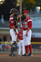 Batavia Muckdogs catcher Blake Anderson (26) talks with pitcher Jeffrey Kinley (30) during a game against the Mahoning Valley Scrappers on June 23, 2015 at Dwyer Stadium in Batavia, New York.  Mahoning Valley defeated Batavia 11-2.  (Mike Janes/Four Seam Images)