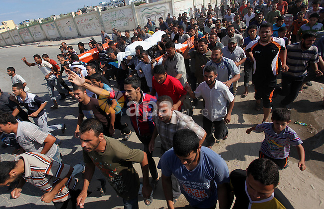 Palestinian mourners carry the body of a Palestinian from Abu Hadaf family, whom medics said was killed along with two other family members by an Israeli air strike, during their funeral in Khan Younis in the southern Gaza Strip August 9, 2014. Israel launched more than 20 aerial attacks in Gaza early on Saturday and militants fired several rockets at Israel in a second day of violence since a failure to extend an Egyptian-mediated truce that halted a monthlong war earlier this week. The Israeli military said that since midnight it had attacked more than 20 sites in the coastal enclave where Hamas Islamists are dominant, without specifying the targets. Medical officials in Gaza said two Palestinians were killed when their motorcycle was bombed and the bodies of three others were found beneath the rubble of one of three bombed mosques. The air strikes which lasted through the night also bombed three houses, and fighter planes also strafed open areas, medical officials said. Photo by Ramadan El-Agha