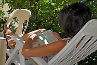 Woman sitting in a deck chair in the garden with her feet up reading a book.