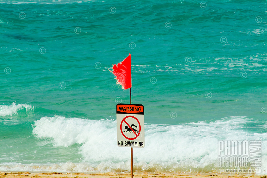 A red flag warns swimmers of high surf at the north shore on the island of Oahu.