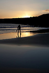 Woman walking on Red Strand, in Dunowen, near Galley Head, West Cork