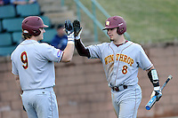 Catcher Babe Thomas (8) of the Winthrop University Eagles is congratulated by John Menken (9) after scoring a run in a game against the University of South Carolina Upstate Spartans on Wednesday, March 4, 2015, at Cleveland S. Harley Park in Spartanburg, South Carolina. Upstate won, 12-3. (Tom Priddy/Four Seam Images)