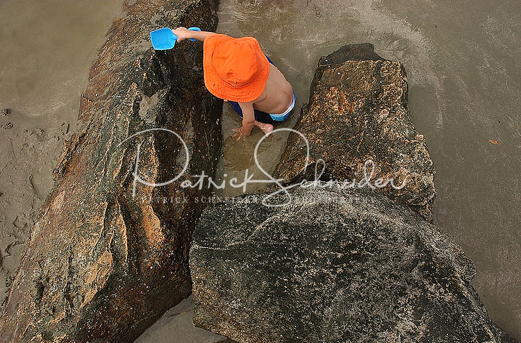 A child inspects large rocks sticking out of the sand along a beach on Sullivan's Island, near Charleston, SC.  Model released image.