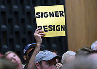 A protestor holds up a sign asking for Mayor Mike Signer to resign during the Charlottesville City Council meeting Monday night in Charlottesville, Va. Photo/Andrew Shurtleff