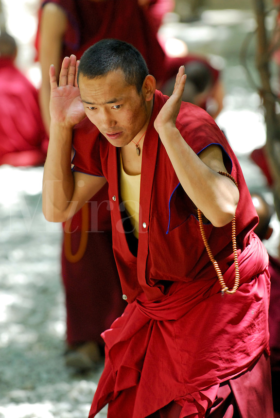 Gelugpa monk, with mala beads, debates Buddhist philosophy in the courtyard at Sera monastery, Lhasa, Tibet, China.