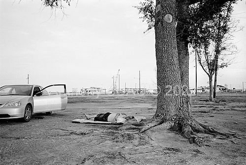Gulf Port, Mississippi.July 30,  2006..A man sleeping by the port that remains destroyed after being hit by hurricane Katrina one year ago..