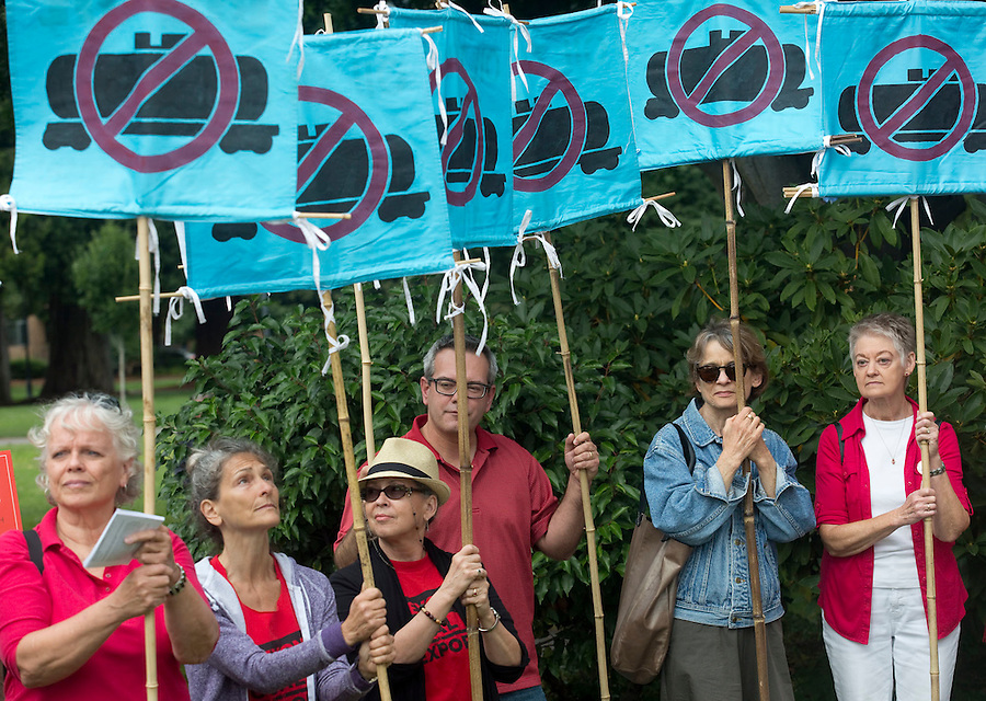 Protesters stand with signs and listen to speeches in Esther Short Park in Vancouver Monday July 18, 2016. Demonstrators opposing the Vancouver Energy oil terminal rallied at the park and marched down to nearby train tracks ahead of a city council meting. (Photo by Natalie Behring/ for the The Columbian)