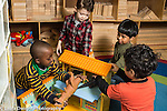 Education preschool 4 year olds group of boys playing together with plastic dinosaurs and doll house