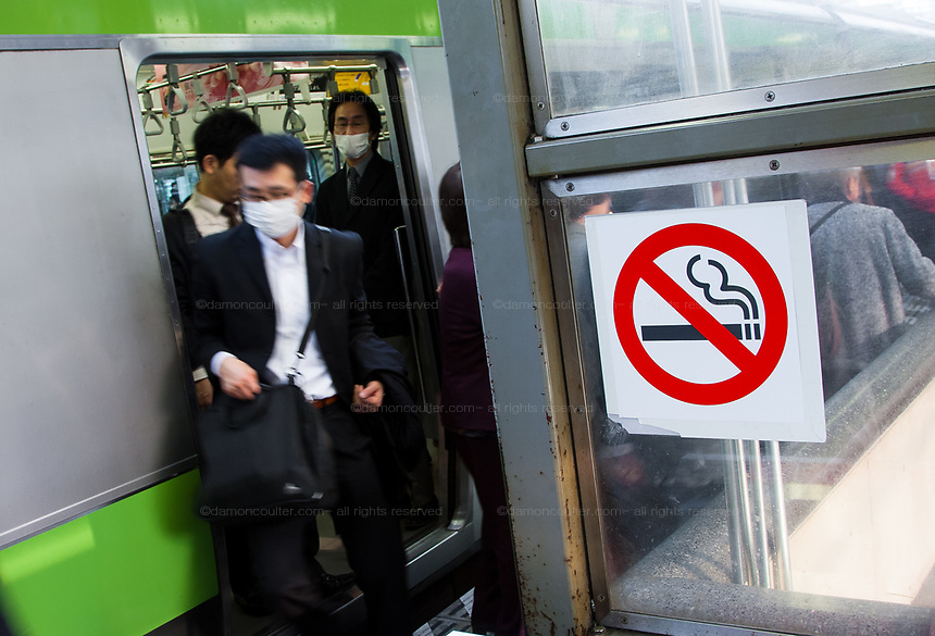 A salaryman or office worker get off a Yamanote line train at Shimbashi station with a no smoking sign on display. Most Tokyo JR (Japan Railways) stations are now no-smoking areas. Tokyo, Japan Wednesday, April 8th 2009