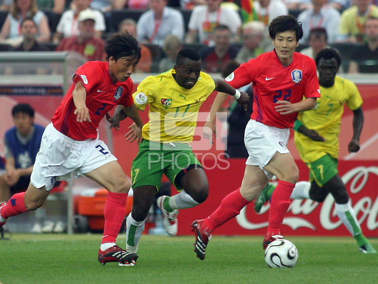 Togo's Kader Mohamed (17) splits Korea Republic's Young Chul Kim (2) and Chong Gug Song (22). Korea Republic defeated Togo 2-1 in their FIFA World Cup Group G match at the FIFA World Cup Stadium, Frankfurt, Germany, June 13, 2006.