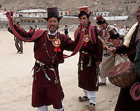 Men performing the traditional dance while wearing their traditional Goncha robes, hats and sashes.