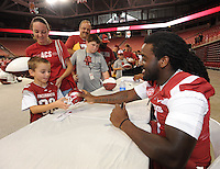 NWA Media/ANDY SHUPE - Samuel Carter, 7, of Nashville, left, smiles as University of Arkansas sophomore running back Alex Collins of Fort Lauderdale, Fla., returns a small football helmet after autographing it as Saumel's mother, Erin Carter, stands alongside during the annual  University of Arkansas Fan Day Sunday, Aug. 17, 2014, at Bud Walton Arena in Fayetteville. The day featured opportunities to have items autographed by members of the Razorbacks volleyball, soccer, football teams, mascots and the spirit squads. Visit photos.nwaonline.com to see more photos from the event.