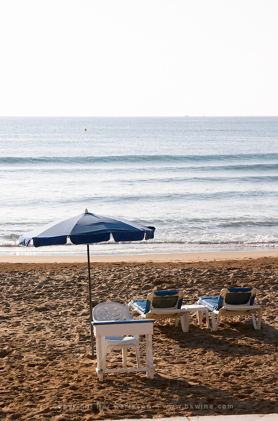 The beach. Two empty deck chairs and a parasol. A plastic chair and parasol for the cashier attendant. Sitges, Catalonia, Spain