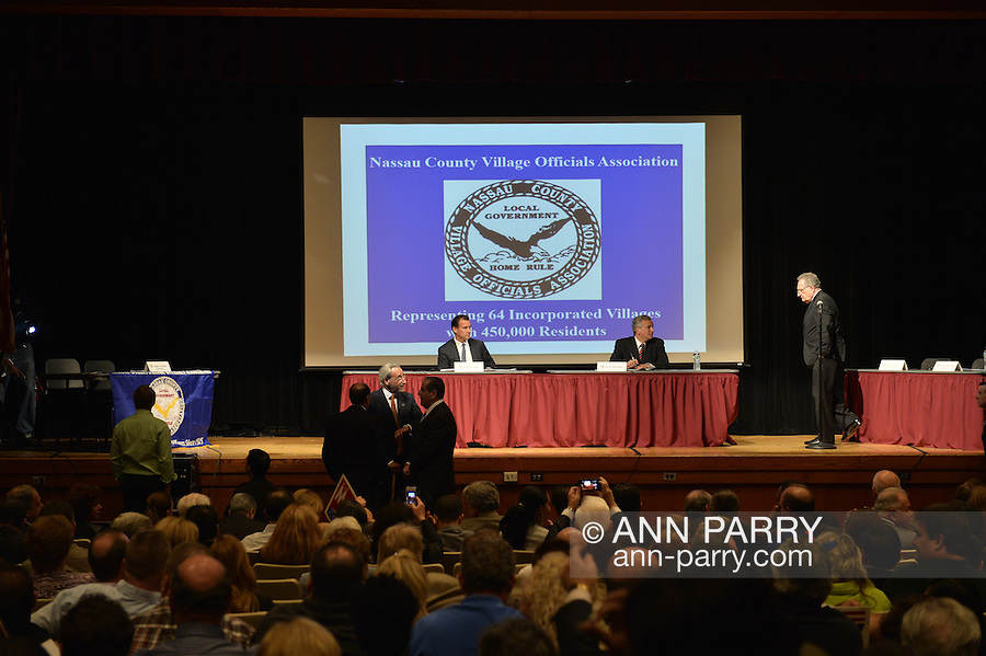 Old Westbury, New York, U.S. 8th October 2013. Republican EDWARD MANGANO, the Nassau County Executive, and Democrat THOMAS SUOZZI, the former County Executive, R-L at red table, are about to face each other in a debate hosted by the Nassau County Village Officials Association, representing 64 incorporated villages with 450,000 residents, as the opponents face a rematch in the 2013 November elections.