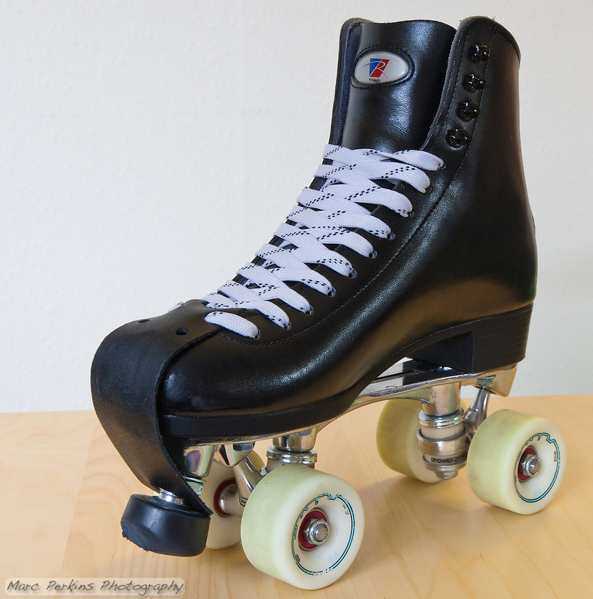 """My current pair of roller skates.  The boots are Riedell 120's in black, the plate is a PowerDyne Triton with toe stop, and the wheels are Radar Riva's 96A 57mm.  The laces are white Sport Mate """"gorilla strength"""" waxed laces.   The wheels have Bones China Reds bearings, and there is a Riedell leather toe protector strap installed."""