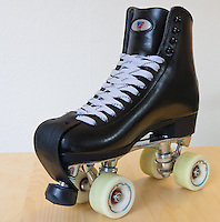 "My current pair of roller skates.  The boots are Riedell 120's in black, the plate is a PowerDyne Triton with toe stop, and the wheels are Radar Riva's 96A 57mm.  The laces are white Sport Mate ""gorilla strength"" waxed laces.   The wheels have Bones China Reds bearings, and there is a Riedell leather toe protector strap installed."