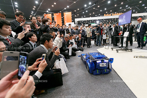 Visitors take pictures of J-deite Quarter a robot transforming between humanoid and vehicle during SoftBank Robot World 2017 on November 21, 2017, Tokyo, Japan. SoftBank Robotics organized SoftBank Robot World 2017 to introduce AI (Artificial Intelligence) and IoT (the Internet of Things) companies developing the latest technology for robots, including applications its humanoid robot Pepper in various business fields. The robot expo runs until November 22. (Photo by Rodrigo Reyes Marin/AFLO)