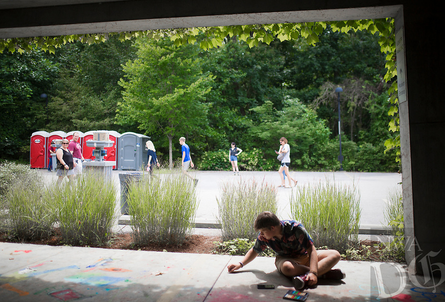 NWA Democrat-Gazette/CHARLIE KAIJO Wyatt Pollet of Bentonville (right) creates chalk art during the first annual chalk festival, Sunday, August 10, 2019 at Crystal Bridges in Bentonville.<br /> <br /> 23 professional chalk artists turned concrete into masterpieces at Crystal Bridges. The artists finished their pieces on Sunday with some 4,000 visitors attending the two-day event. Attendees also enjoyed live music, food trucks and a kids chalking area.