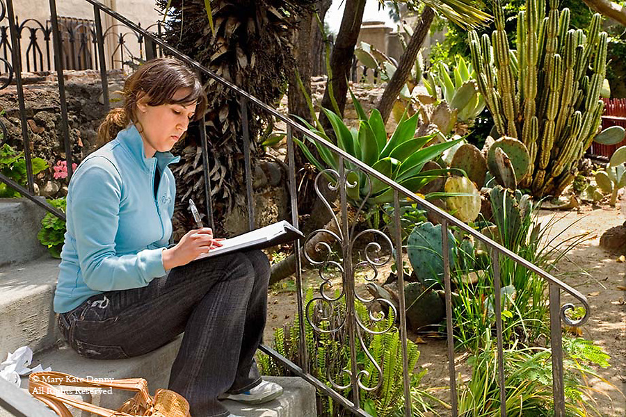 One 25+female sits on stone steps in mission garden sketching plants for.landscape class