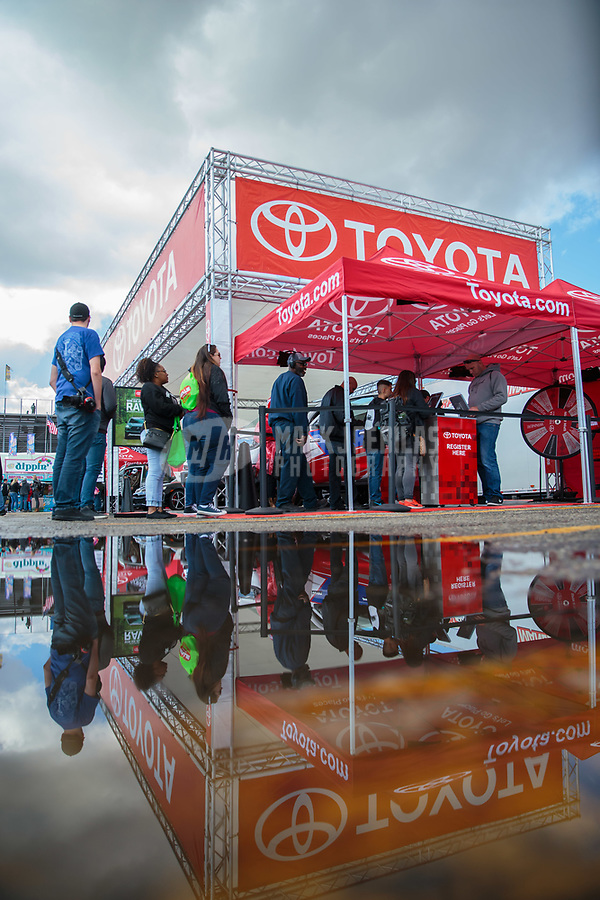 Feb 9, 2019; Pomona, CA, USA; NHRA fans reflect in a rain puddle at the Toyota hospitality display on the midway during qualifying for the Winternationals at Auto Club Raceway at Pomona. Mandatory Credit: Mark J. Rebilas-USA TODAY Sports