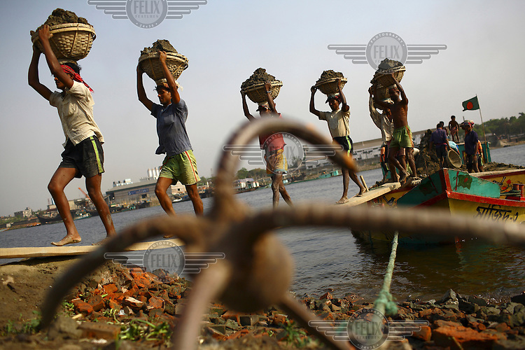 A line of labourers carrying loads of clay from a barge. The clay will be used to manufacture bricks.