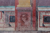 Frescoes including a face and trompe l'oeil details along the bottom of the cryptoporticus in the Casa del Criptoportico, or House of the Cryptoporticus, Pompeii, Italy. The house is one of the largest in Pompeii and was owned by the Valerii Rufi family and built in the 3rd century BC. It takes its name from the underground corridor or cryptoporticus used as a wine cellar and lit by small windows. Pompeii is a Roman town which was destroyed and buried under 4-6 m of volcanic ash in the eruption of Mount Vesuvius in 79 AD. Buildings and artefacts were preserved in the ash and have been excavated and restored. Pompeii is listed as a UNESCO World Heritage Site. Picture by Manuel Cohen