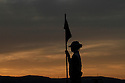 A silhouette of a caddie holds the flag at sunset at the Trent Jones  Jnr  designed Spring City Golf Course  at Kunming, Yunnan Province, China on 14th March 2011 Picture Credit / Phil Inglis.....
