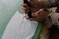 MAY 15, 2014 - KOJIMA, KURASHIKI, JAPAN: Kengo Oshima cuts Denim fabric for hand made ordered jeans at the Betty Smith's factory. (Photograph / Ko Sasaki)
