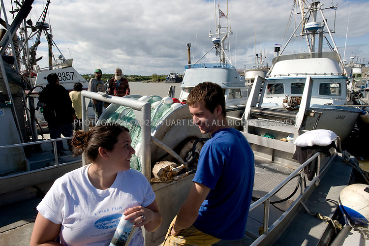 8/4/2008--Dillingham, AK, USA..Justin Pleier, 22 (right) and his fiance Carrie Benedict 24 (left) on their fishing boat in Dillingham Port while other fishermen prepare to head out for a night fishing for salmon in Bristol Bay.    Like many fisherman in the region, they oppose the proposed Pebble mine.  The Pebble Mine site is currently being drilled to map deposits of ore for possible extraction. The mine contains large deposits of copper, gold, and molybdenum and is in the Bristol Bay region of Southwest Alaska, near Lake Iliamna. The proposal to build a large mine is controversial and opponents say it threatens nearby wild salmon runs from Bristol Bay into the nearby watersheds. .The mine is being explored by Pebble Ltd Partnership, a joint venture of  Northern Dynasty Partnership and Anglo American US LLC. The mine  would probably include an open pit and large dams to contain waste. Bristol Bay is home to some of the largest runs of salmon in the world and the world's largest sockeye salmon fishery. It's also a popular sport fishing area, and subsistence fishing is important to the region's native communities...©2008 Stuart Isett. All rights reserved.