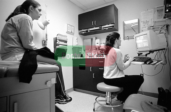 Young female internal medicine resident physician seated at computer listens to young female patient seated on examination table in examination room