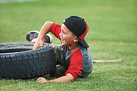 A young fan smiles after falling while rolling a tire to the mascot during a Batavia Muckdogs on field promotion, The Dizzy Tire Race, during a game against the Brooklyn Cyclones on July 5, 2016 at Dwyer Stadium in Batavia, New York.  Brooklyn defeated Batavia 5-1.  (Mike Janes/Four Seam Images)