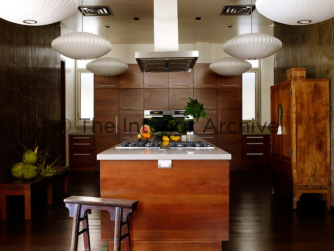 George Nelson pendant lights seem to float from the kitchen ceiling in which contemporary units are mixed with an antique Korean cabinet and a Chinese stool