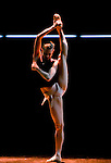 Rambert Dance Company, A dancer stretches before a performance of 21. Choreographer: Rafael Bonachela