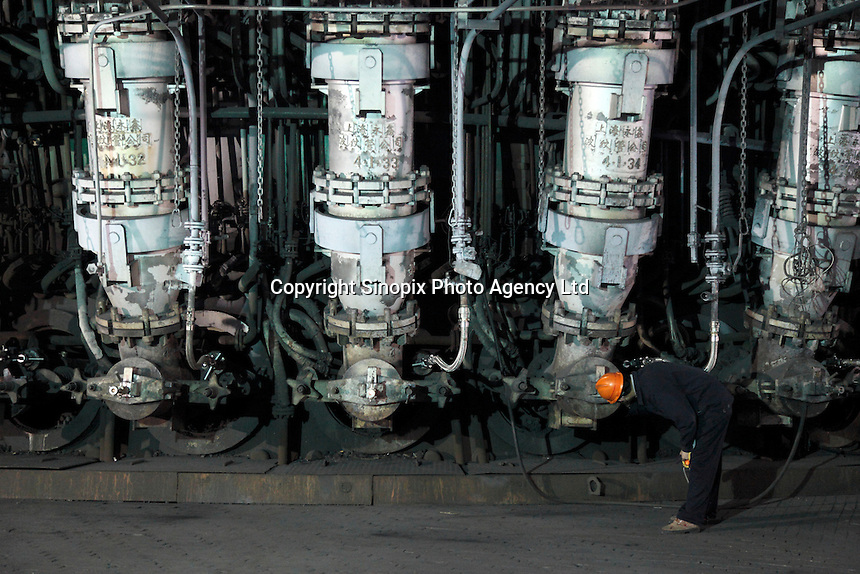 A worker checks the temperature of the iron smelter at Ma Steel's new plant in Maanshan, China..29 Dec 2008..